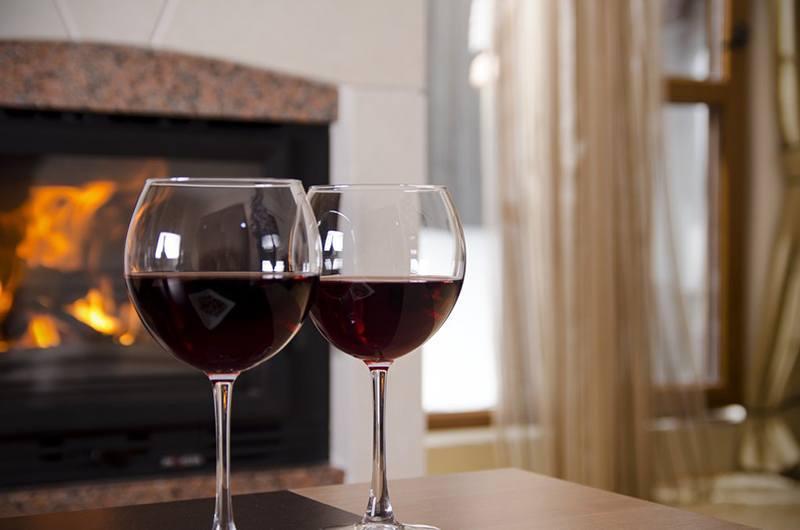 чаши червено вино и запалена камина