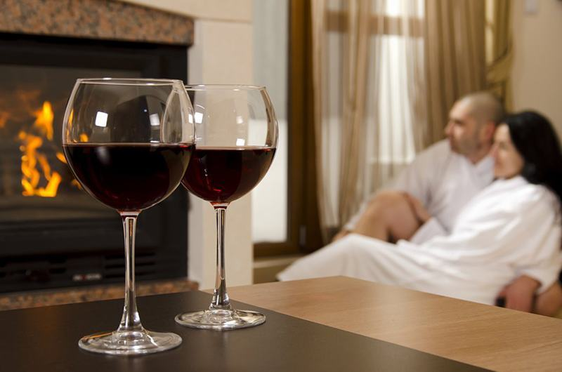 двойка пред запалена камина и чаши вино